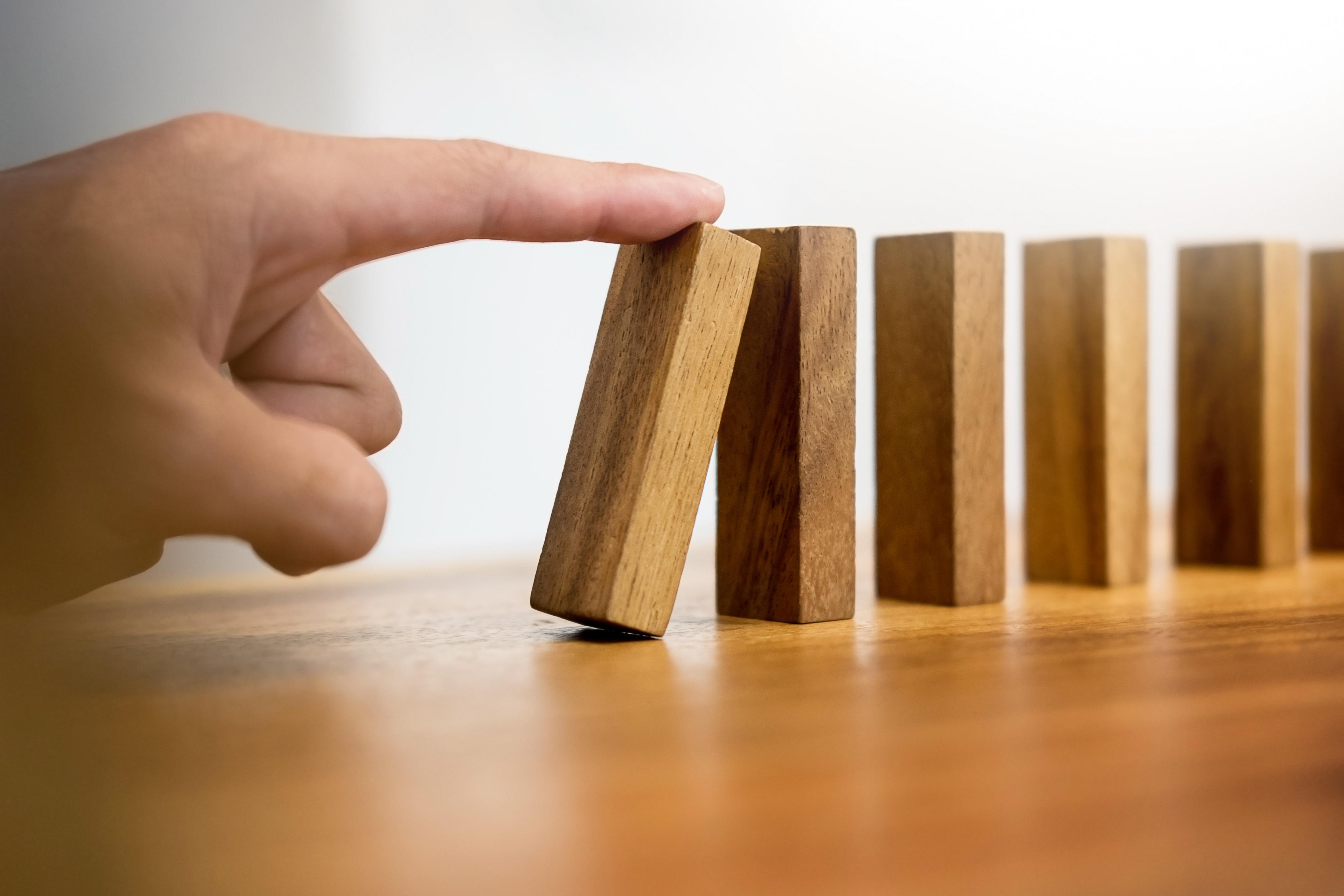 Hand Pushing Dominos stock photo